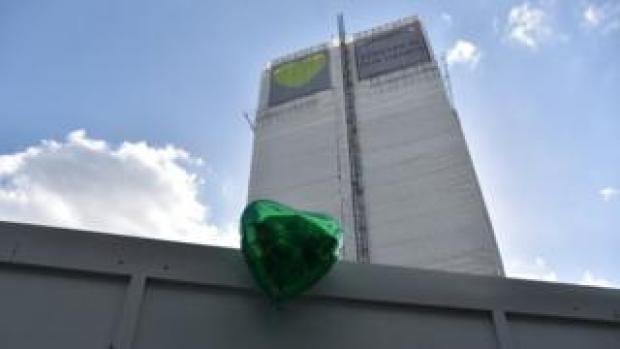 A green balloon by a memorial wall next to Grenfell Tower