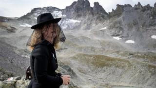 "A woman takes part in a ceremony to mark the ""death"" of the Pizol glacier"