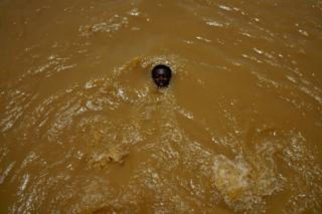 A boy head is seen above the water. His eyes are closed, and the rest of his body is submerged.