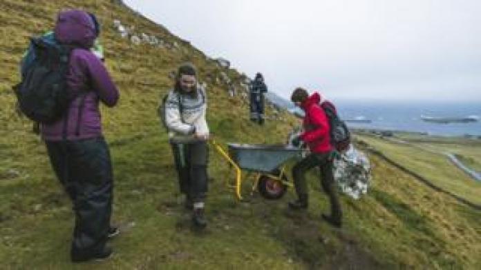Brown Group members help each other to push a wheelbarrow in the hills in Kirkjubøur