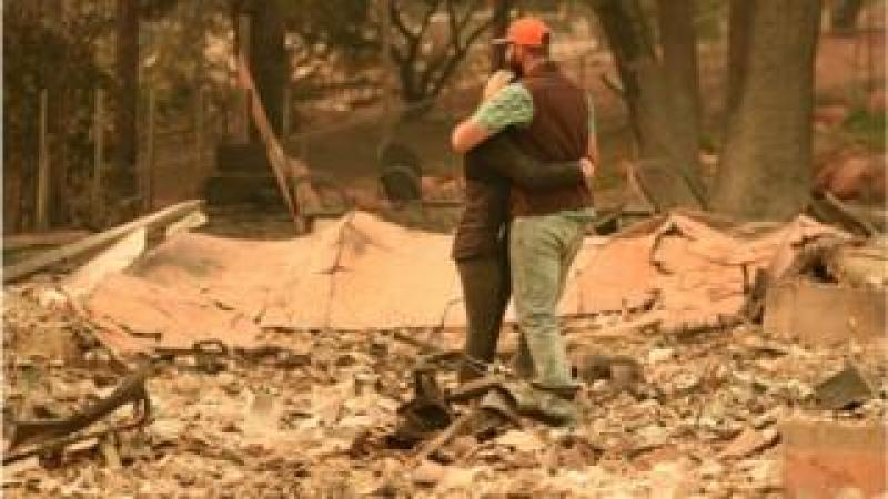 A couple embraces while looking over the remains of their burned residence after the Camp fire tore through the region in Paradise, California