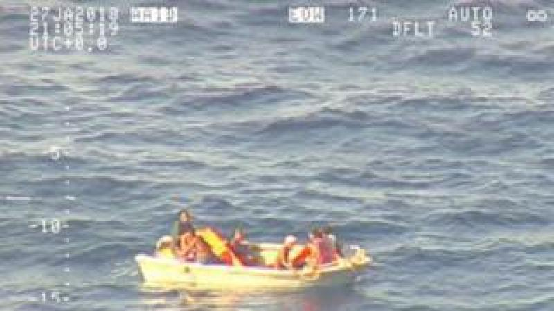A pixellated image from an aircraft shows seven people clustered in a small pale dinghy