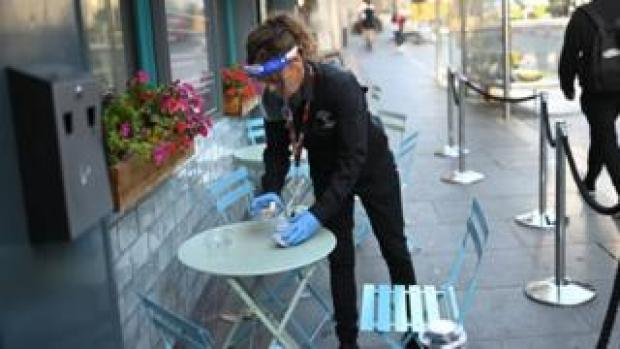 A waitress clearing a table in Liverpool