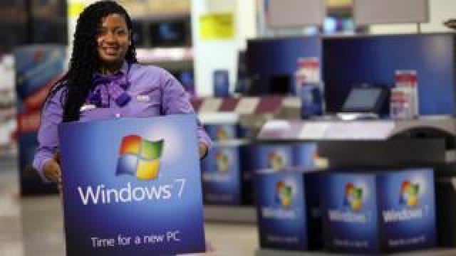 Someone holding a Windows 7 PC box.