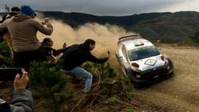 People take pictures of a rally car