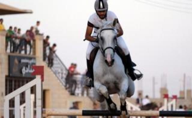 A rider on his horse jumps over a barrier during the Knights of Libya Festival in Benghazi, Libya - Tuesday 7 August 2018