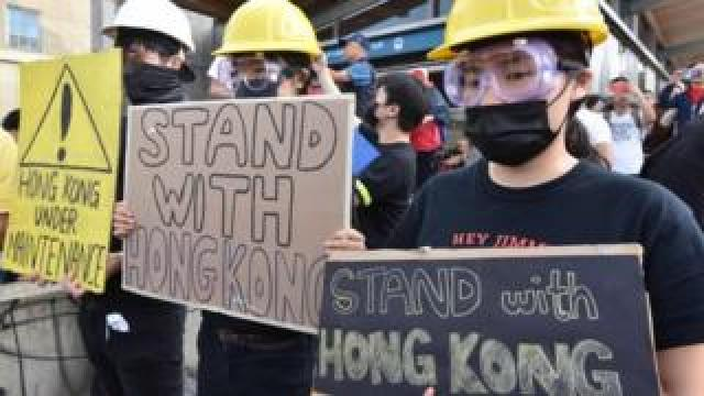 Hong Kong pro-democracy supporters hold signs during a rally in Vancouver