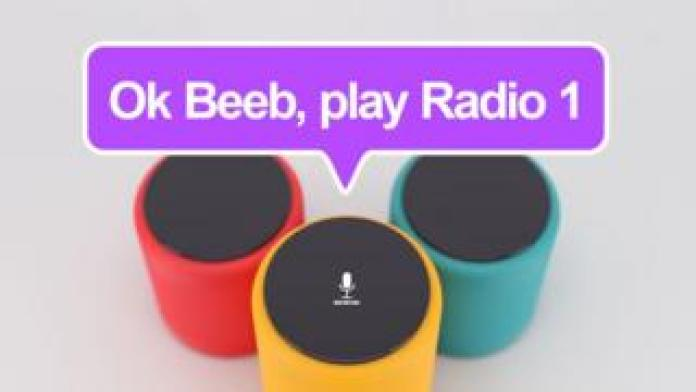 "A photo illustration shows a floating speech bubble over three smart speakers, with the speech bubble reading ""Ok Beeb, play Radio 1"""