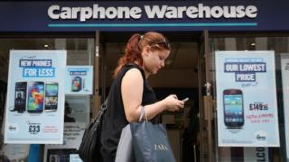 Woman walks past Carphone Warehouse store