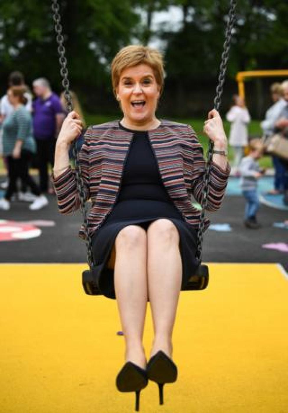 First Minister Nicola Sturgeon sits on a swing