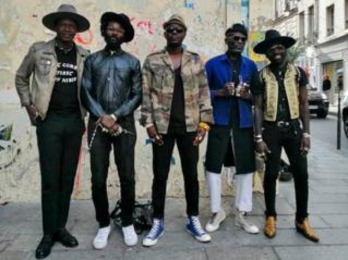 Amah Ayivi wearing Marche Noir on streets of Paris with friends