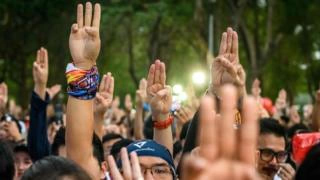 "Participants gesture a three-finger salute at the start of a ""run against dictatorship"" in Bangkok"