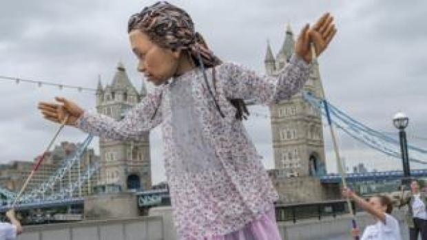 Little Amal in front of Tower Bridge