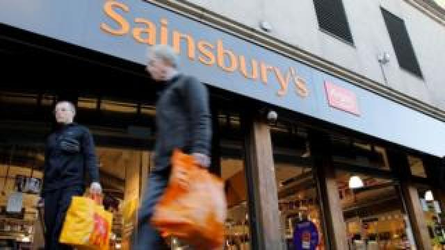 Two people walk past a Sainsbury's store