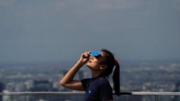 A woman watches the eclipse in Bangkok