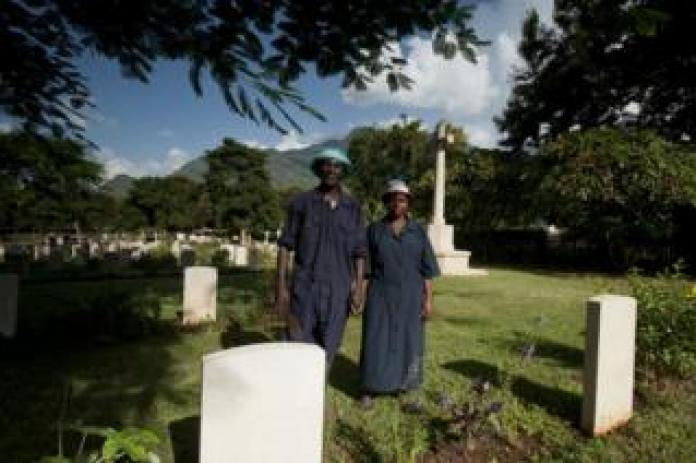 Shadrack Paull and Lusia Axalte hold hands among graves in cemetery in Tanzania