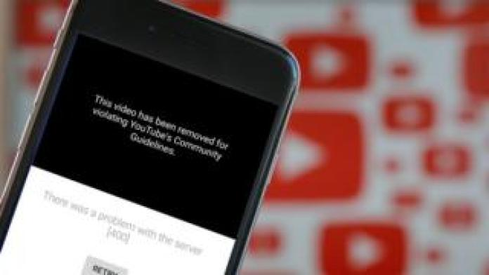 A photo illustration shows the YouTube app on a mobile phone with the message that the video has been removed