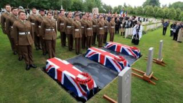 The coffins of two young privates and an unknown soldier, who fought during World War One, during a burial service at Hermies Hill British Cemetery near Albert, France.