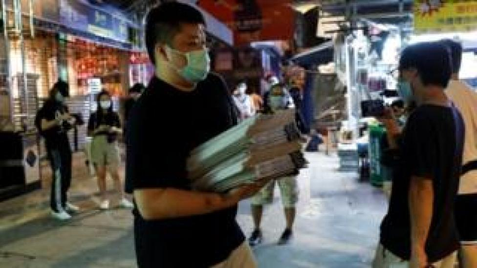 A man buys a pile of Apple Daily newspapers in Hong Kong