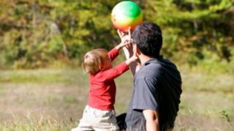 A man playing with a ball with a little boy
