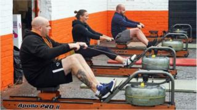 People using rowing machines outside a gym