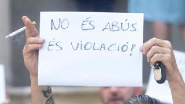 The girl's uncle holds up a placard outside the court in Barcelona, 3 July