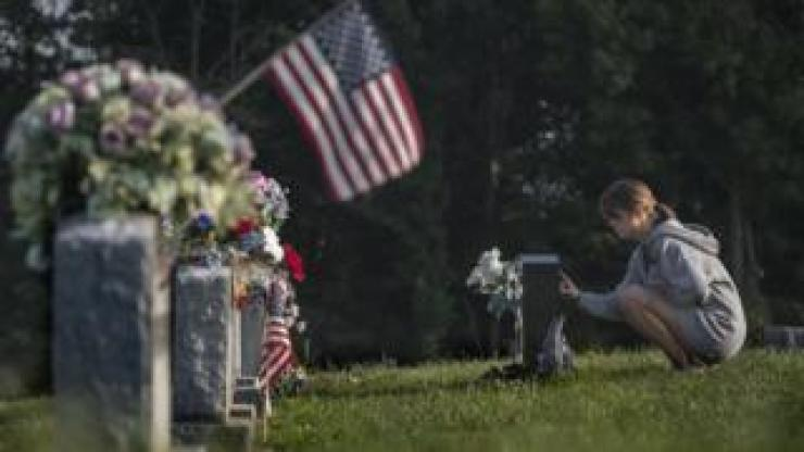 A woman mourns at a gravestone in Austin, Indiana