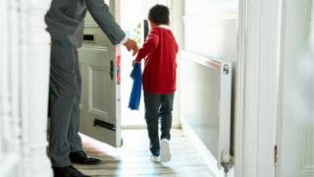 Boy going out of his door to school