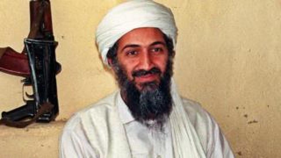 Image of smiling Osama bin Laden with firearm in background