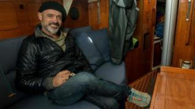 Argentine sailor Juan Manuel Ballestero poses for a picture in the cabin of his sailboat