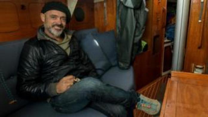 Argentine sailor Juan Manuel Ballestero poses for a photo in the cabin of his sailboat