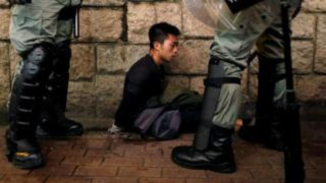 Riot police officers detain an anti-extradition bill protester