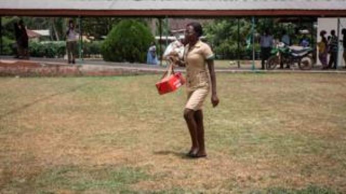 nurse walks across a field carrying medical supplies
