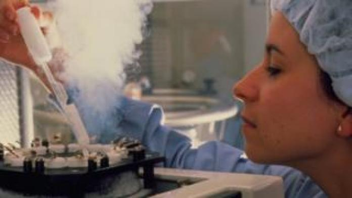 Frozen embryos being removed from storage