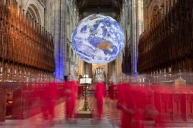 Choristers and a replica of the Earth in Peterborough Cathedral