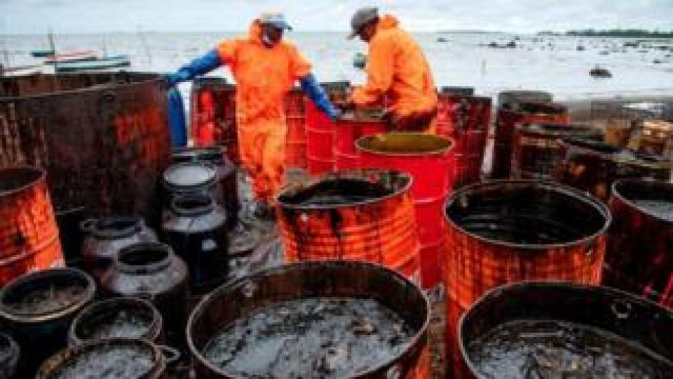 Workers collect leaked oil at the beach in Riviere des Creoles on August 15, 2020
