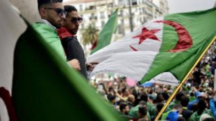 Algerian protesters wave a national flag as they take part in a demonstration in the capital Algiers on May 3, 2019. - Algerians gathered for an 11th consecutive Friday of demonstrations.