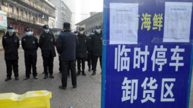 Security guards stand in front of a closed seafood market in Wuhan, which has been linked to the outbreak