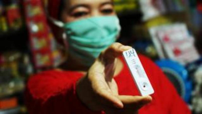 Woman holding a coronavirus test kit