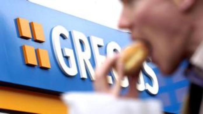 Man eating a pasty from Greggs