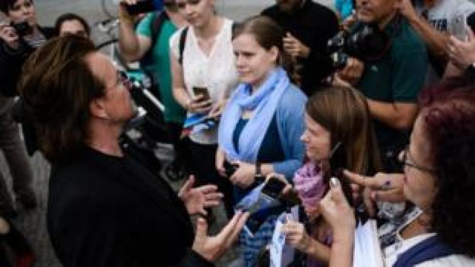 Le chanteur du groupe de rock irlandais U2 s'entretient avec les fans après une visite à la chancelière allemande Angela Merkel (pas sur la photo), devant la chancellerie de Berlin, en Allemagne, le 28 août 2018