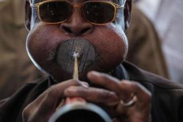 A man puff his cheeks out as a he plays a horn. He is wearing glasses. A Sudanese man plays a local music instrument ahead of a meeting with Mohamed Hamdan Dagalo, also known as Himediti, deputy head of Sudan's ruling Transitional Military Council (TMC) and commander of the Rapid Support Forces (RSF) paramilitaries, in the capital Khartoum on June 18, 2019.