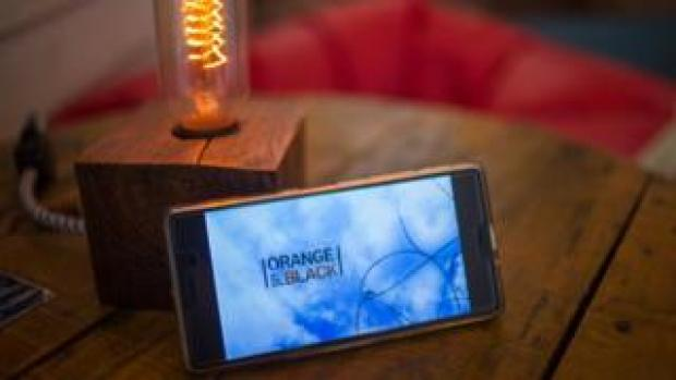 A smartphone with the Orange is the New Black logo