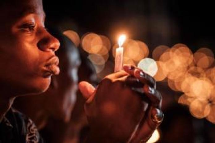A person holds a candle during a night vigil and prayer at the Amahoro Stadium in Kigali