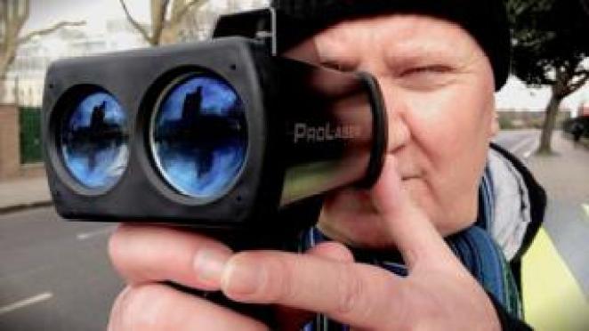 A volunteer speed detector clocks a motorist with his laser gun