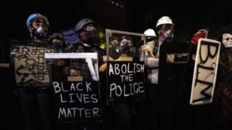 Gas-masked protesters in Portland holding Black Lives Matters placards
