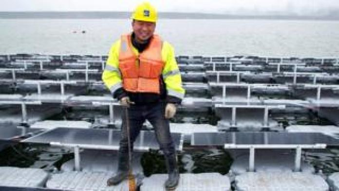Wu Wenhui in yellow hard hat and orange life jacket standing on floating solar panels
