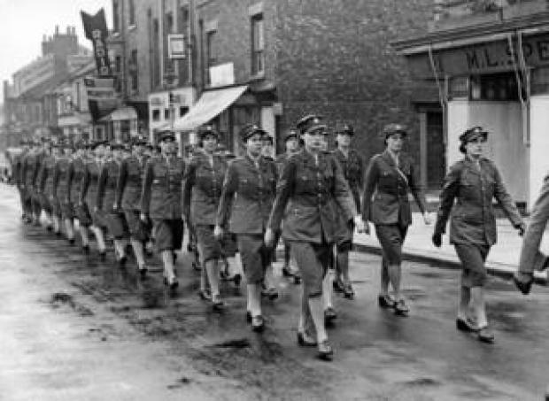 A VE Day parade of uniformed servicewomen marching down the street