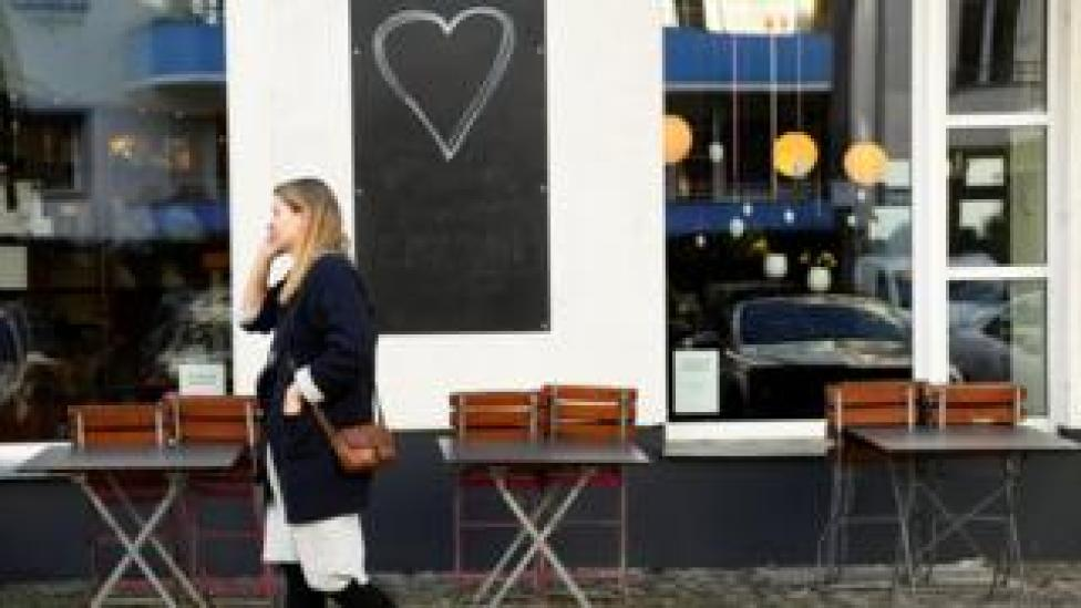 Piled chairs and tables are seen in front of a chocolate store in Berlin