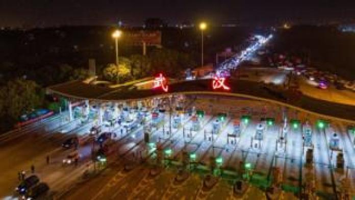 This aerial photo taken early on April 8, 2020 shows cars driving through a highway toll station in Wuhan in China's central